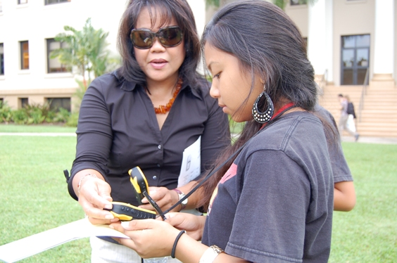 Lorna Ramiscal, GEAR UP Waipahu assistant director, helps a student with her GPS device.