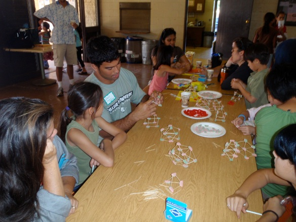 "Several parents and children gather at the ""Platonic Solids"" station led by Fellow Zachary Lee-Ho from the UH Mānoa Native Hawaiian Science & Engineering Mentorship Program."