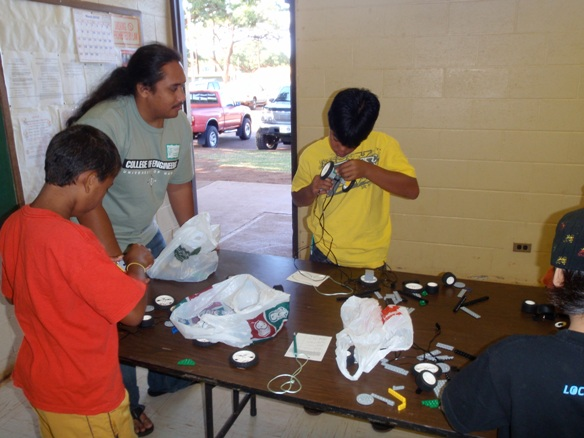 Native Hawaiian Science & Engineering Mentorship Program Fellow Nelson Fernandez engages and encourages two youngsters to put their skills to good use at the robotics station.