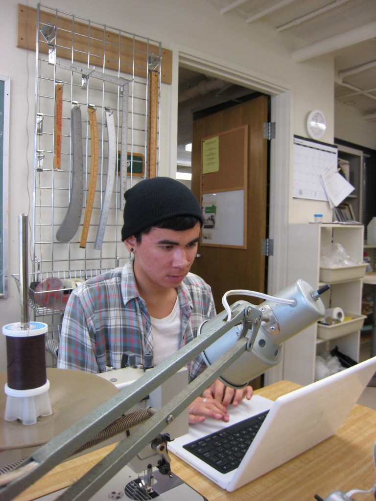 Fashion merchandising major Johnny Lombardi, who is serving as director of the student fashion show on April 25, works on last-minute details.