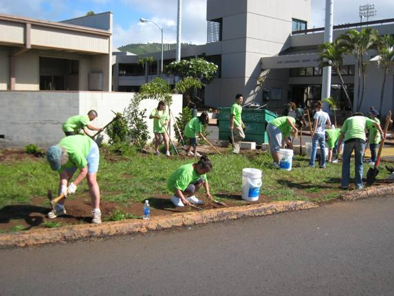 Mānoa Makeover volunteers do some weeding along the Varsity Gate entryway to campus.