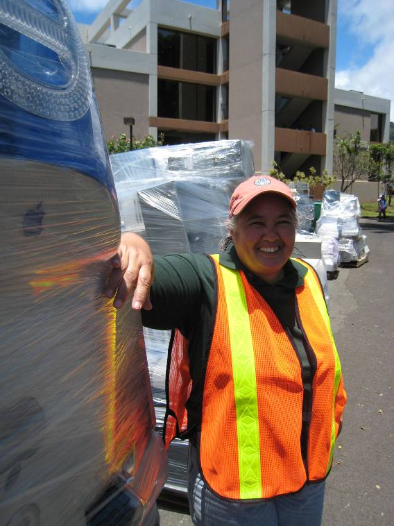 Landscaping manager Roxanne Adams poses with thousands of pounds of electronic waste collected by Pacific Corporate Solutions, which will ship it to California for recycling.