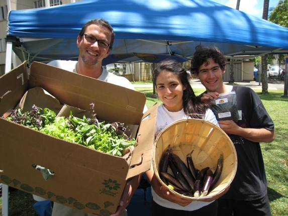 Sustainable and Organic Farm Training students sold products straight from the Student Farm. From left, Josh Neipp holds a box of organic herbs, Jeana Cadby displays a harvest of eggplant, and Gabriel Sachter-Smith offers up a packet of worm compost.