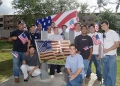Group of students around U.S. flag crafted from sheet metal