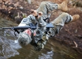 Army cadet crossing river on a rope