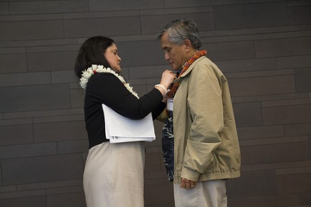 Dr. Palafox prepares to speak at the 2013 Intercultural Cancer Conference, as Dr. Lee Buenconsejo-Lum attaches the microphone to his jacket.