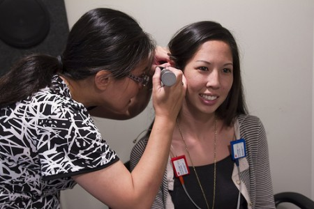 Dr. Chiemi Tanaka demonstrates an exam at the JABSOM-CSD Speech-Hearing Clinic at the Gold Bond Building.