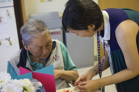 MS1 Mariko Shimizu chats with a Kuakini senior as she helps him assemble his heart craft.